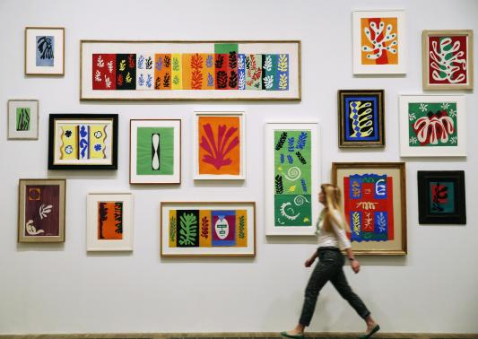 An employee poses with Henri Matisse's artworks at the Tate Modern gallery in London in this April 14, 2014 file photo. Credit: REUTERS/Luke MacGregor/Files