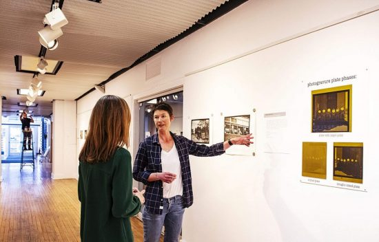 Trace Nichols explains her process to Sarah Roy, left, during the installation of the new show at the Red Brick Arts Center on Friday, March 6, 2020. (Kelsey Brunner/The Aspen Times)