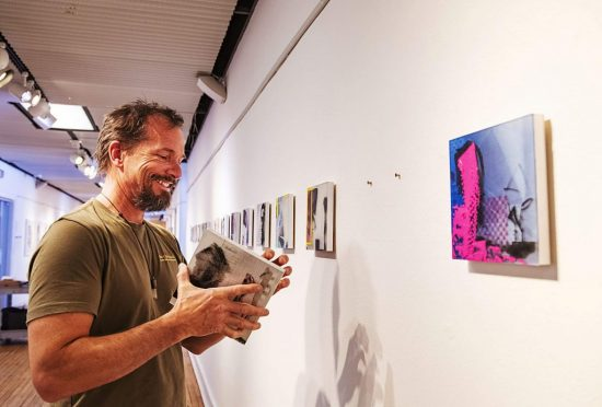 Teran Hughes helps install the work of Andrew Roberts-Gray for the upcoming Red Brick Arts Center show on Friday, March 6, 2020. (Kelsey Brunner/The Aspen Times)
